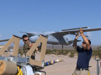 Navy and Insitu personnel lift the RQ-21A Small Tacticall Unmanned Aircraft System (STUAS) onto launcher in prepartion for flight at Naval Air Station China Lake, Calif. Sept. 10. (U.S. Navy Photo)